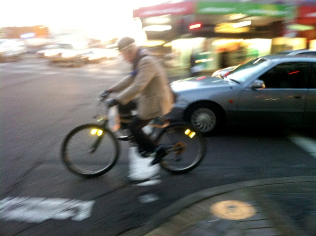 Elderly cyclist with walking stick on bike